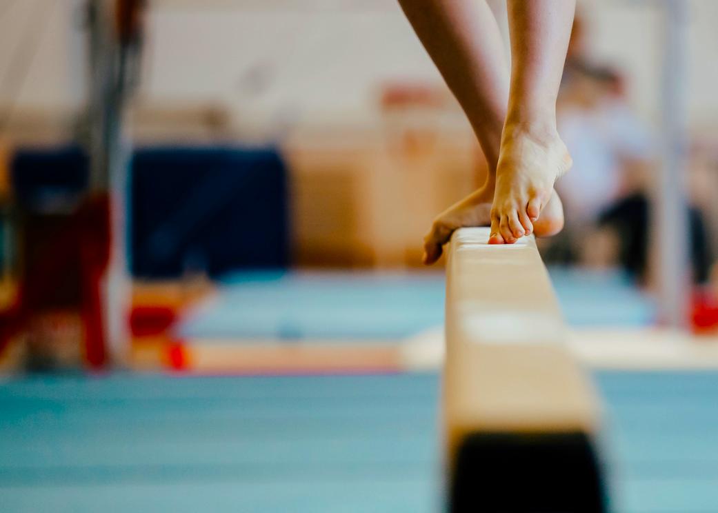 A gymnast's feet on a balance beam